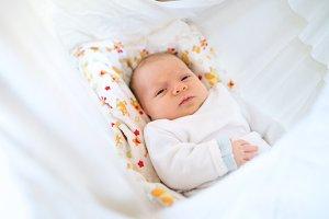 Cute happy newborn baby lying on bed
