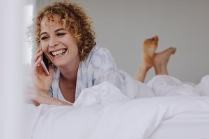 Woman talking on mobile phone lying