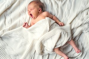 Newborn baby lying on bed, covered