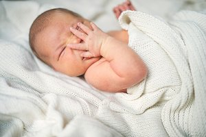 Newborn baby with a hand on her face