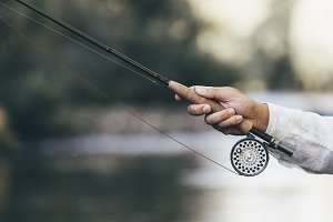 Fly fishing rod in fisherman hand