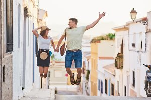 Happy young couple of travellers jum