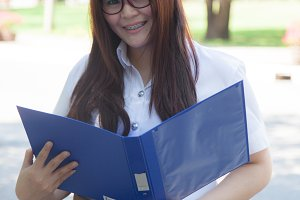 Student holding a blue documents.