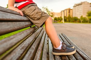 Boy legs sitting on the top of bench