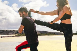 young adult couple stretching togeth