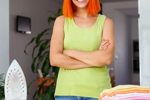 Redhead woman ironing clothes at hom