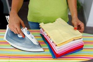 Woman ironing colorful shirts