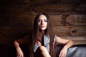 Beautiful young girl sitting on sofa