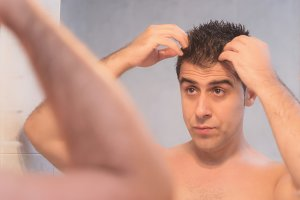 Handsome man applying hair gel