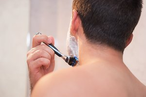 Handsome man shaving his beard