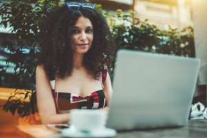 Appealing curly girl with laptop