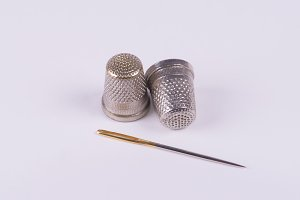 Two thimbles with a needle