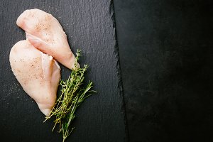 Raw chicken breast on dark backgroun