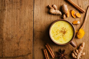 Hot turmeric milk with spices on woo