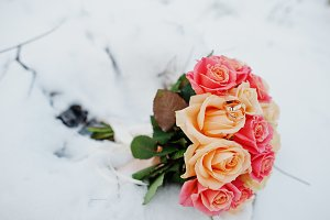 Wedding bouquet with rings at snow.