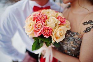 Bouquet of roses in hands of couple.