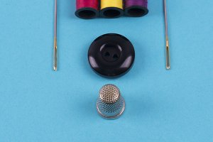 Button, needles, thimble and thread