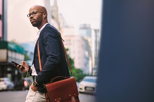 African businessman with bag walking