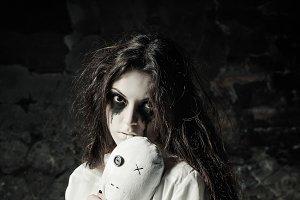 Sad strange girl with moppet doll