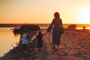 mother walks with children on the be