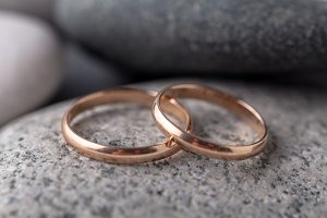 Gold wedding rings lie on rock