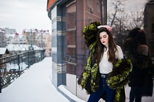 Brunette girl in green fur coat at s