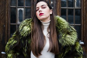 Brunette girl in green fur coat agai