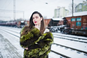 Brunette girl in green fur coat on t