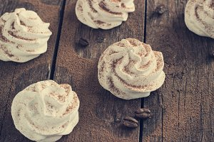 white meringue on a dark wooden background retro