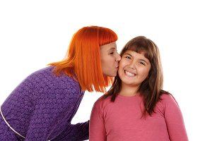 Red haired woman kissing her daughte