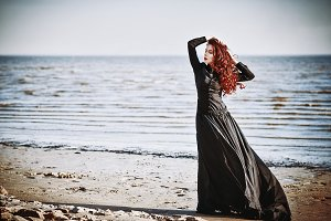 Beautiful sad goth girl on sea beach