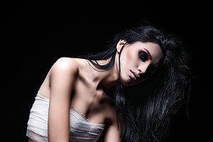 Sad young beautiful girl among dark