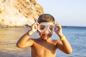 Kid with diving goggles on the shore