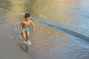 Litttle kid running on the the shore