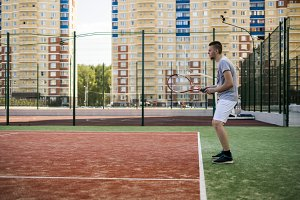 young man playing tennis on court in