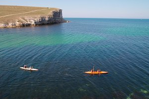 Kayakers sculling on the sea.