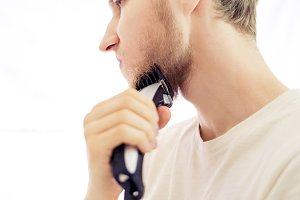 isolated young hipster shaving beard