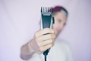 young male hipster holds a shaving m