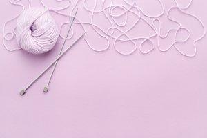 Lilac yarn with knitting needles