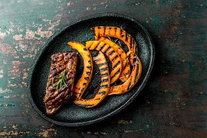 Grilled meat and pumpkin on black