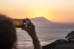 Woman taking photos of a sunset
