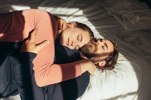 Couple sleeping on bed together