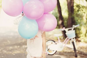 Little girl holding colorful balloon
