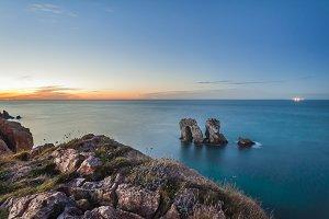Rocks in te ocean water at sunset