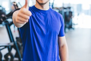 Happy man standing at the gym, showi