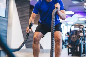 Man exercising with ropes at the gym