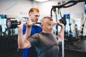 Senior man lifting weights with help