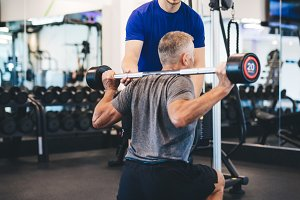 Senior man exercising with personal