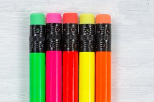 Colorful pencil tip erasers on wood