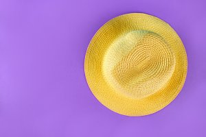 Yellow summer hat on a purple backgr